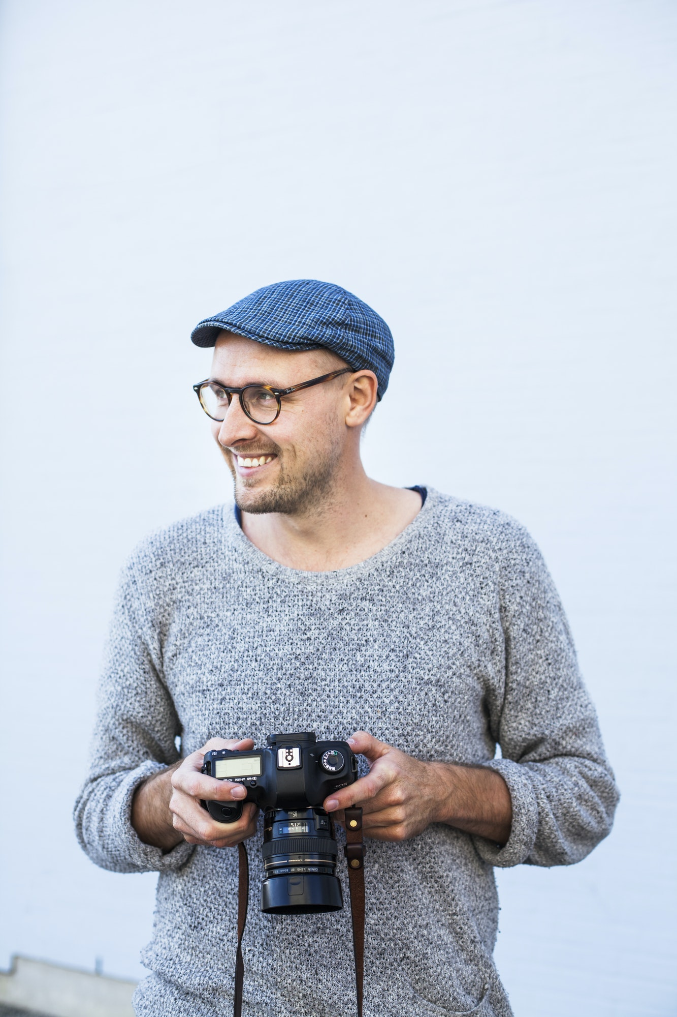 Happy man holding digital camera against wall
