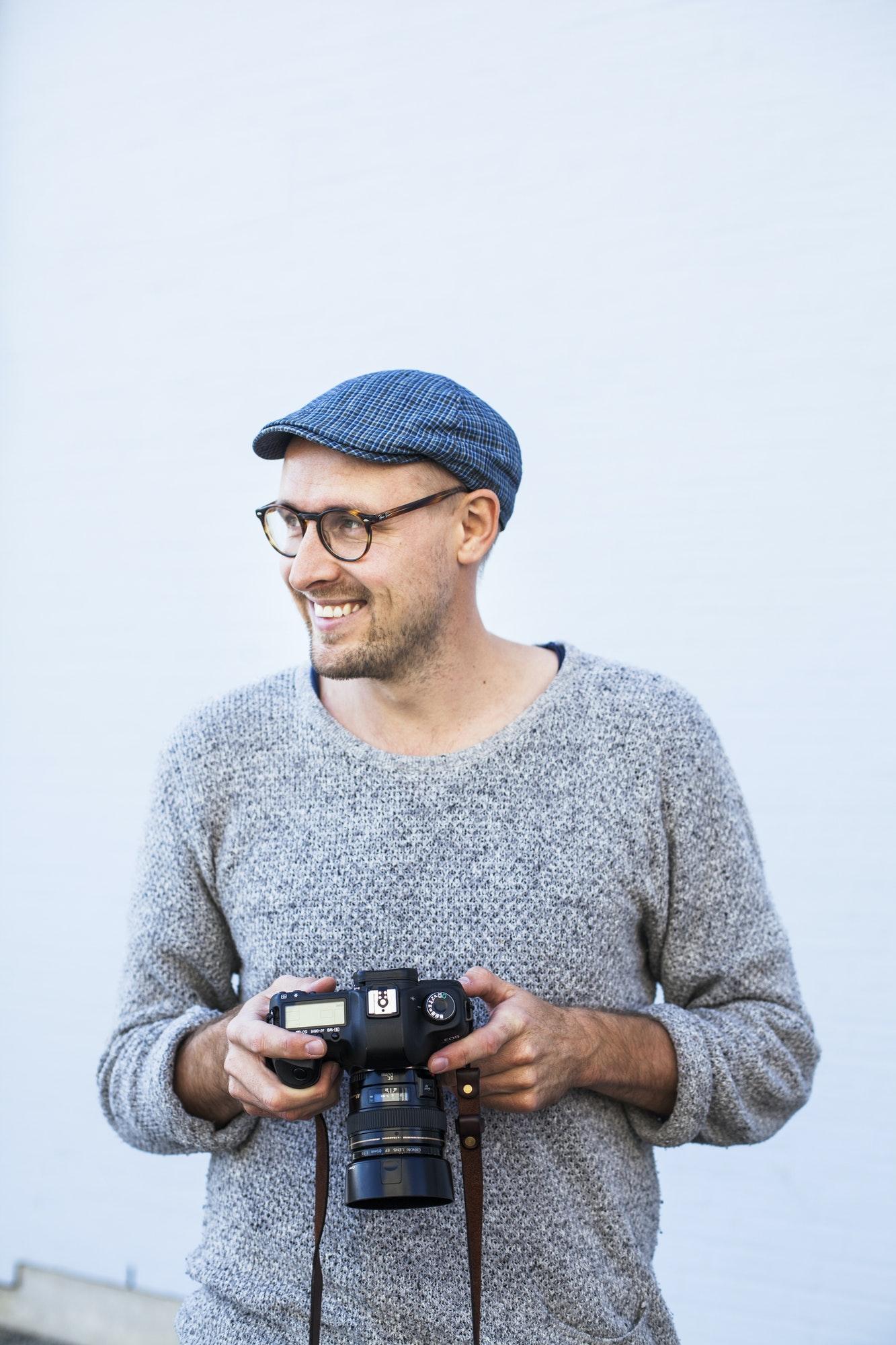 Happy man holding digital camera against wall